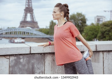 active sports woman in sport clothes stretching against clear view of the Eiffel Tower in Paris, France.