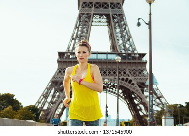 active sports woman in sport clothes not far from Eiffel tower in Paris, France jogging.