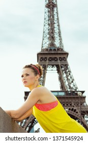 active sports woman in sport clothes not far from Eiffel tower in Paris, France looking into the distance and relaxing after workout.