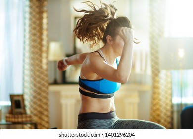 active sports woman in sport clothes in the modern house workout.