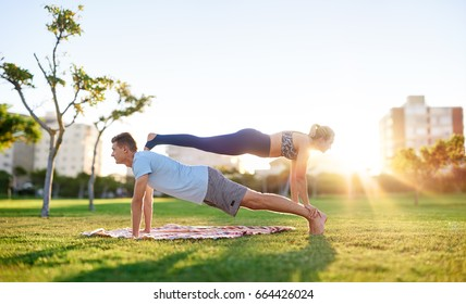 Active sporty couple working out together on grass, strength training planking at sunset, bonding exercise