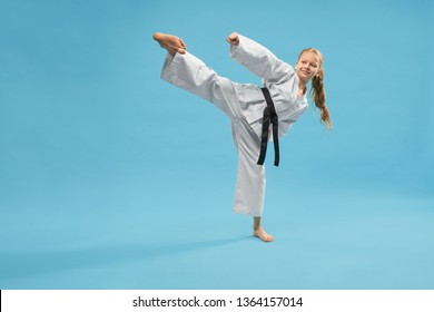 Active sporty girl wearing kimono kicking with leg on blue isolated background. Smiling female child doing taekwondo and practising jujitsu in studio. Concept of training process.