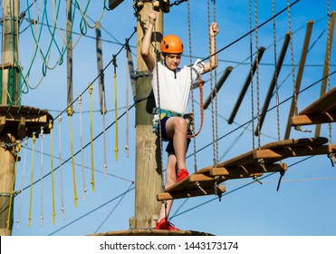 Active sporty kid in helmet doing activity in adventure park with all climbing equipment. Active children climb on the trees and having fun outdoors. Summer camp