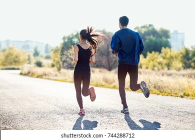 Active sporty woman and man jogging on sunny day in park. Couple in tracksuits running along the road. Healthy lifestyle, sport, healthcare concept. Full-length portrait of two people, back view