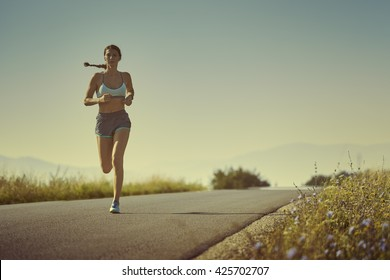 Active sporty woman in summer sportswear running, sprinting on a road at sunrise or sunset. Health care, body care, healthy lifestyle, willingness concept. Toned color edit.