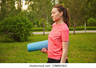 Active sporty woman training outdoors. Female stanging in a park and holding sport mat