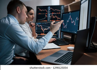 Active talking. Team of stockbrokers are having a conversation in a office with multiple display screens.