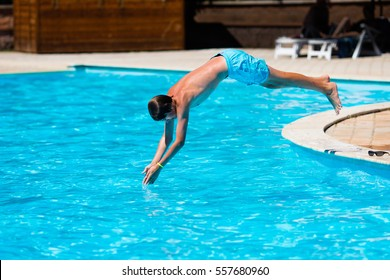 Active teenager boy jumping into an outdoor pool from spring board learning to dive during sport class on a hot summer day.