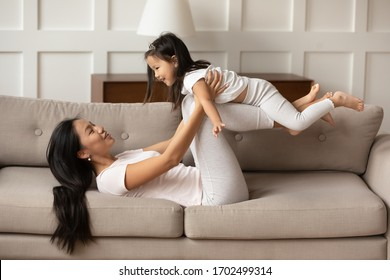 Active time with kid at home, joint rest with children and travel together concept. Asian mother lying on couch in living room lift little daughter while she raised hands imagines herself like plane
