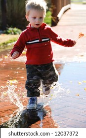 active toddler splashes through huge puddle in the fall