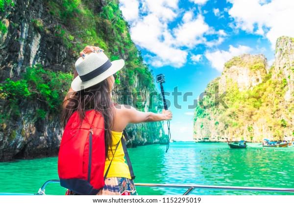 Active traveler Asian girl joy and fun on boat using action cam take photo Phi let lagoon Krabi, Travel nature Phuket Thailand, Tourism beautiful destination Asia, Tourist summer holiday vacation trip