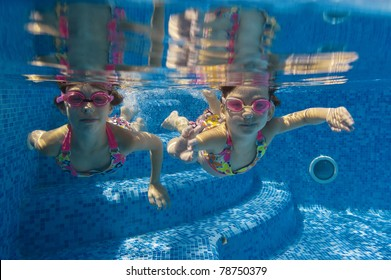 Active underwater kids in swimming pool. Girls swim and having fun. Child sport on summer vacation