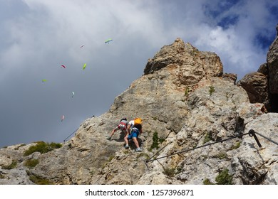 Active vacation activities in the Dolomites (Dolomiti mountains in Italy): via ferrata rock climbing and paragliding on a sunny day of summer