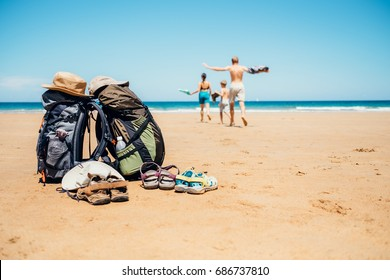 Active vacation concept image. Backpacker travelers family happy to swim in ocean waves