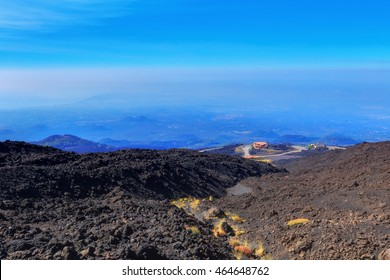 Active Volcano Etna on Sicily, Italy. Mountain and Hills Landscape with burned black magma earth. Black ground and blue sky