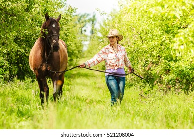 Active western cowgirl woman in hat walking with horse. American girl in countryside ranch.