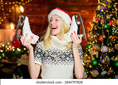 Active winter. Winter sports. Ideas for leisure. Skater christmas gift. Woman Santa hat with figure skates. Cheerful girl with pair of skates. Winter fun christmas holidays. Equipment outdoor sport.