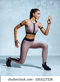 Active woman doing front forward one leg step lunge exercise. Photo of woman performs exercises for legs on grey background. Strength and motivation