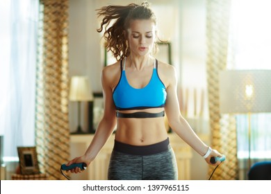 active woman in fitness clothes exercise using a jump rope with heart rate monitor at modern home.