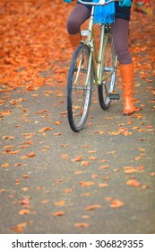 Active woman girl riding bike bicycle relaxing in fall autumn park. Healthy lifestyle and recreation leisure activity.