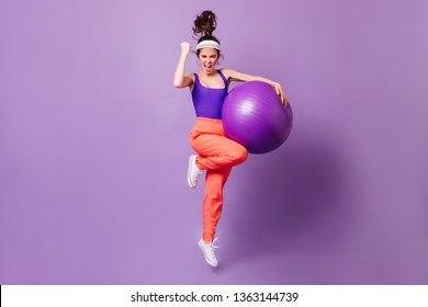 Active woman happily bounces with fitball on purple background. Girl in bright tracksuit in style of 80s enjoys victory