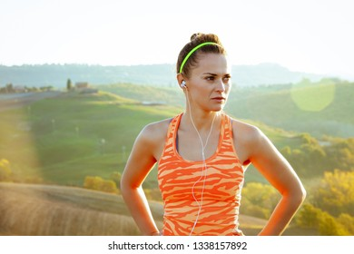 active woman jogger in fitness clothes with headphones in Tuscany, Italy looking into the distance.