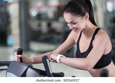Active woman looking at smart watch in a gym
