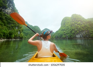 Active woman paddling the kayak in the calm bay Halong among picturesque karst mountains.Vietnam.