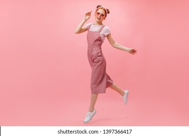 Active woman in pink jumpsuit, T-shirt and stylish glasses moves on pink background
