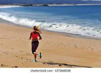 Active woman running on beach on summer