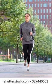 Active woman running outside in the city