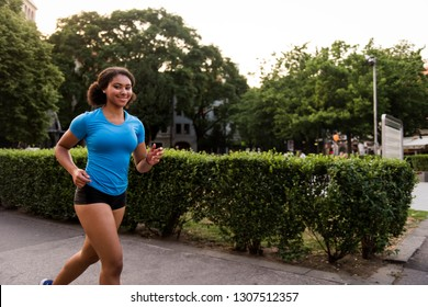 An active woman smiles while running outdoors