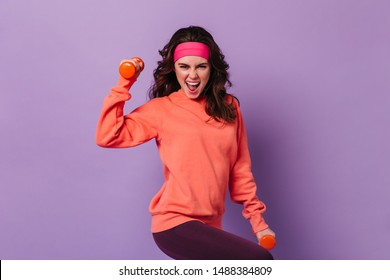 Active woman in sports bright outfit emotionally demonstrates exercises for hands with dumbbells