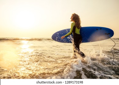 active women with surf board enjoy watersport at vacation holidays.sport girl in surfing school instructor of windsurf. tourist female model in a diving suit wetsuit on the beach in the Indian Ocean