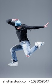 Active young beautiful hip-hop dancer man jump in fly at studio, copy space, motion shot. Grey background