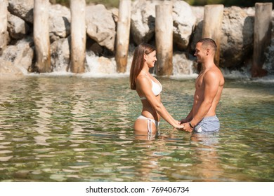 Active young couple chilling out in river  on a hot summer day standing and walking in water