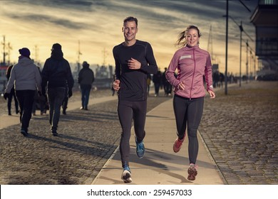 Active young couple jogging side by side on a harbor promenade at sunset during their daily workout in a health and fitness concept