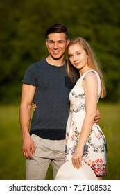 Active young couple on a walk in the park on hot summer afternoon