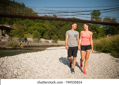 active young couple on a walk on riverbank on hot summer afternoon