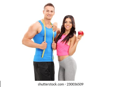 Active young couple posing with an apple isolated on white background