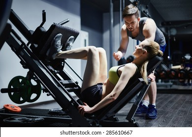 Active young female doing exercise for legs on special equipment in gym