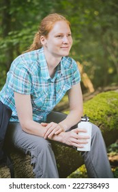 An active young female tourist sits on a tree log in a green forest with a water bottle in her hand.