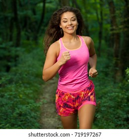 active young fit woman runer runs in green forest on late summer afternoon