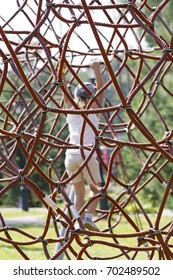 Active young girl climbing the spider web playground activity in summer.