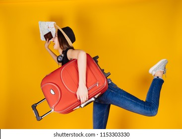 active young girl in a hat and jeans goes on vacation with a big red suitcase