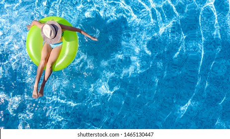 Active young girl in hat in swimming pool aerial top view from above, child relaxes and swims on inflatable ring donut and has fun in water on family vacation, tropical holiday resort