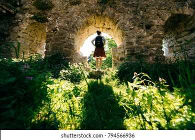 active young girl travels, stands in a ruined ancient building surrounded by greenery
