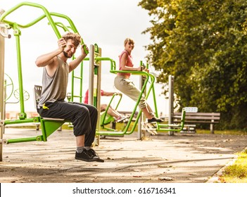 Active young man exercising on chest press machine and woman on leg raise. Muscular strong guy and girl in training suit working out at outdoor gym. Sport fitness and healthy lifestyle concept.