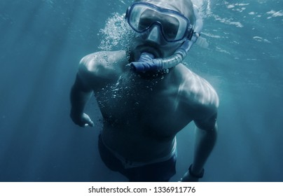 Active young man freediver in mask with snorkel swimming underwater.