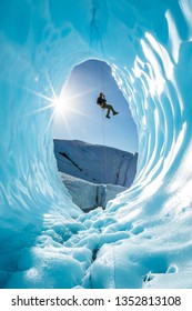Active young man ice climber on glacier rappelling into ice cave entrance in Alaska.